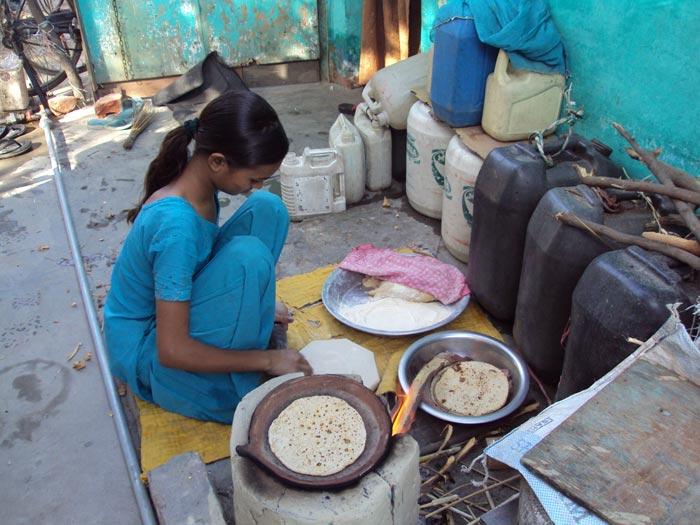 Girl making rotis in Delhi slum - (c) Jill McGivering
